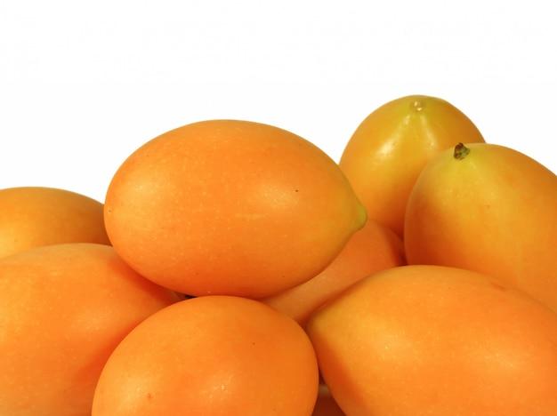 Tas de prunes mariales fraîches jaunes fraîches vibrantes isolées sur fond blanc