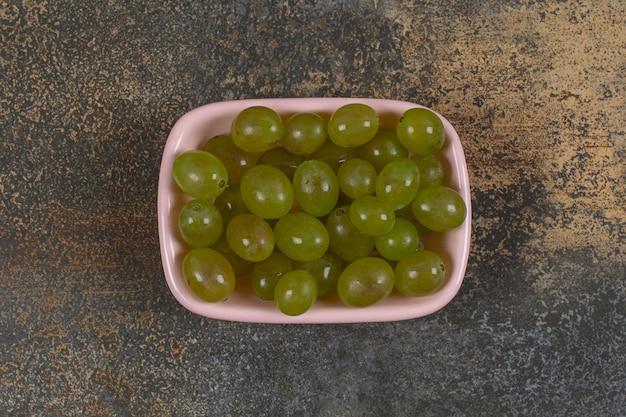 Tas de raisins verts dans un bol rose.