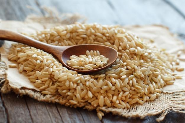 Tas de riz brun avec une cuillère en bois close up