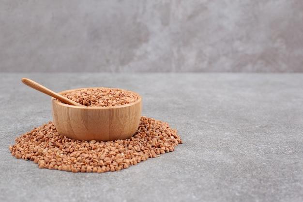 Tas de sarrasin cru dans un bol en bois