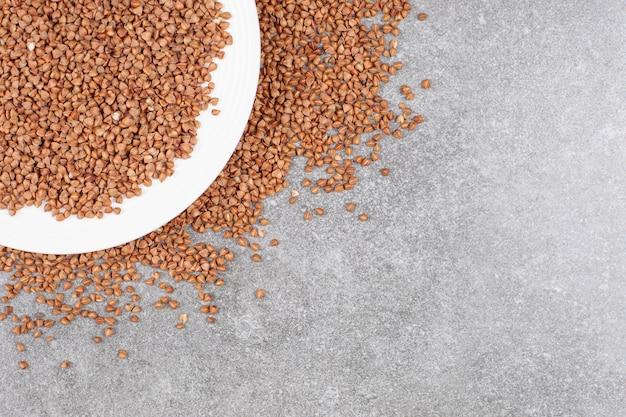 Tas de sarrasin cru sur plaque blanche