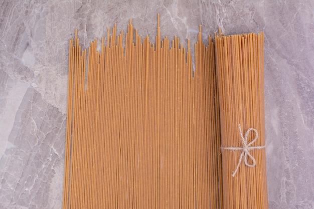 Un tas de spaghetties crues sur un espace gris.