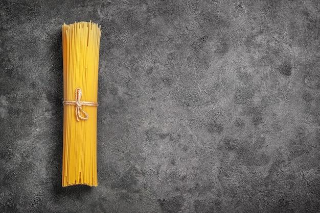 Tas de spaghettis crus attachés avec une corde sur fond noir
