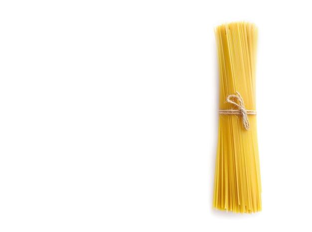 Tas de spaghettis crus attachés avec une corde isolated on white