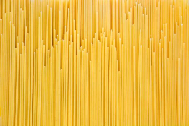 Tas de spaghettis crus jaunes, pâtes jaunes fond noir, prêts pour la cuisson, vue de dessus