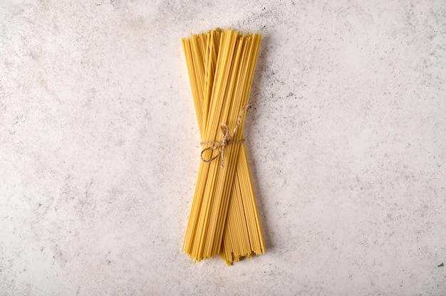 Tas de spaghettis crus non cuits sur fond texturé gris copie espace vue de dessus