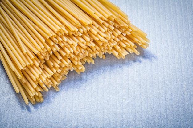 Tas de spaghettis non cuits sur une surface bleue
