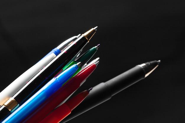 Tas de stylos gros plan sur fond noir foncé