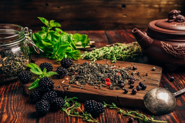 Tas de thé vert sec et de mûres fraîches sur une planche à découper en bois. paquets de feuilles de menthe et de thym. bouilloire en argile.