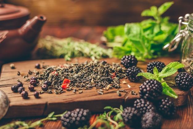 Tas de thé vert sec et de mûres fraîches sur une planche à découper en bois