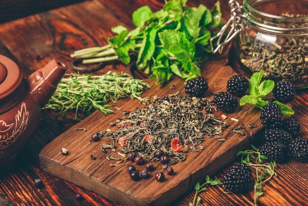 Tas de thé vert sec et de mûres fraîches sur une planche à découper en bois.