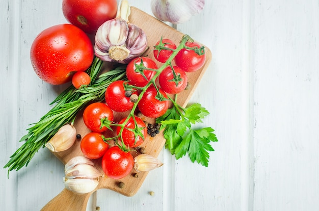 Tas de tomates cerises rouges bio juteuses au romarin vert