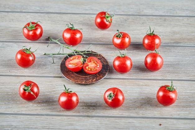 Tas de tomates fraîches juteuses et de tranches de tomate sur table en bois.