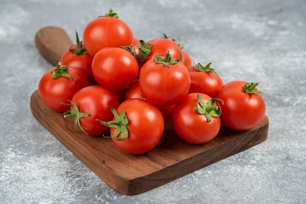 Tas de tomates fraîches rouges sur une planche à découper en bois.