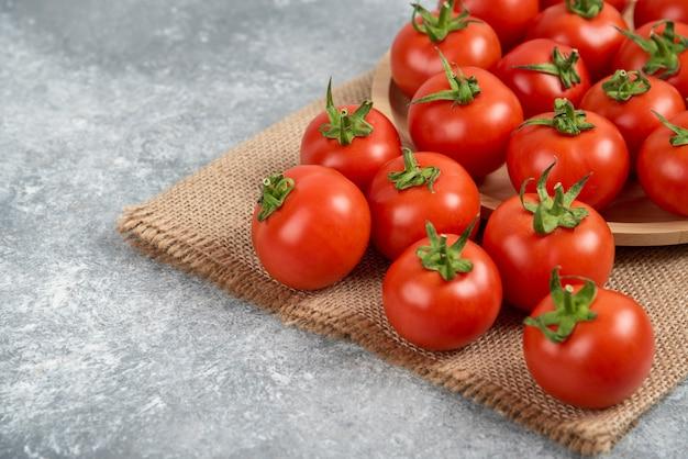 Tas de tomates fraîches rouges avec un sac sur une surface en marbre.