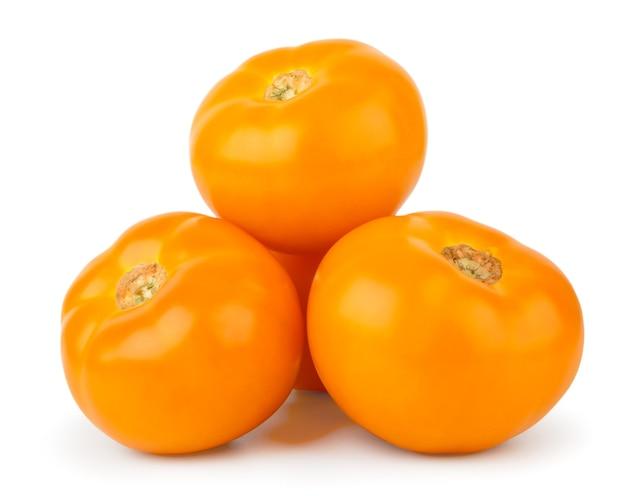 Tas de tomates jaunes bouchent sur un fond blanc