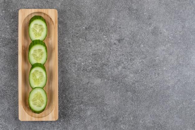 Tas de tranches de concombre frais sur planche de bois.