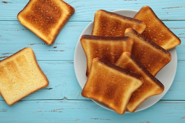 Tas de tranches de pain grillé sur plaque grise sur bleu.