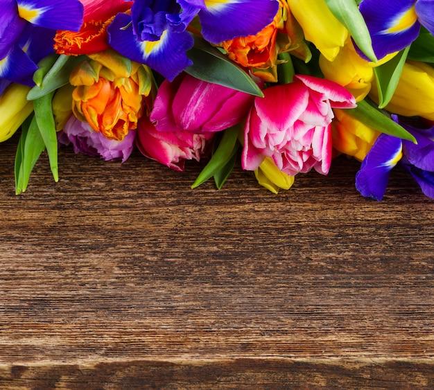 Tas de tulipes printanières et iris boder avec copie espace sur bois