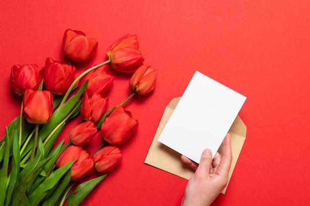 Tas de tulipes rouges et et une feuille de papier blanc sur un fond rouge.