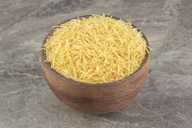 Tas de vermicelles non cuits dans un bol en bois