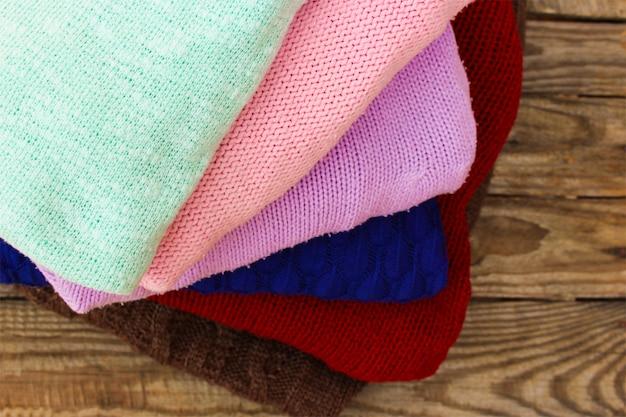 Tas de vêtements chauds colorés sur fond en bois.