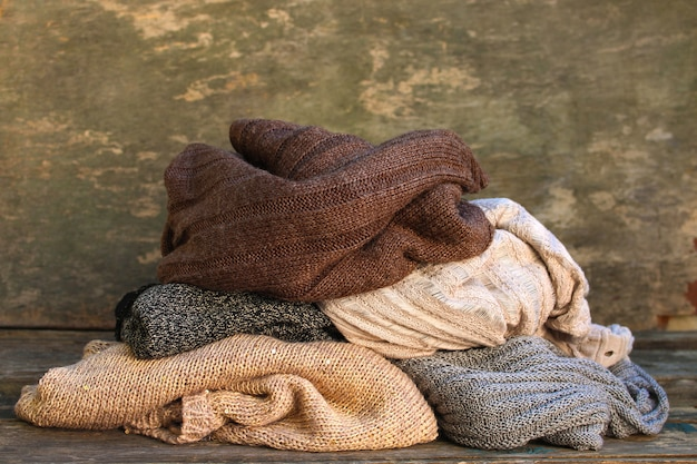Tas de vêtements chauds sur plancher en bois