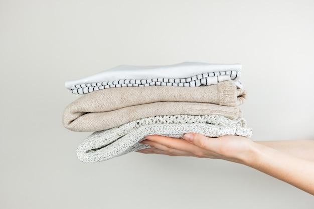 Tas de vêtements dans des mains féminines. vêtements simples soigneusement empilés sur fond blanc