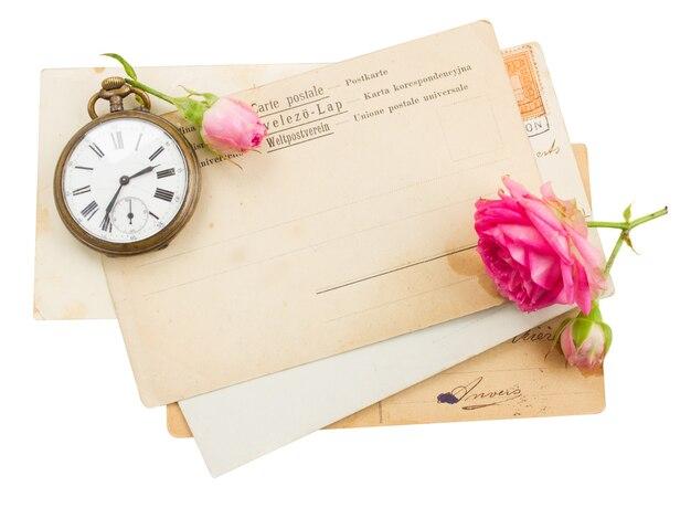 Tas de vieux papiers avec des roses une horloge ancienne