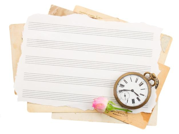 Tas de vieux papiers avec vieille horloge et rose