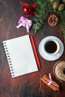 Une tasse d'accessoires de décoration de branches de sapin de thé noir et un cadeau à côté d'un cahier avec un stylo sur fond sombre