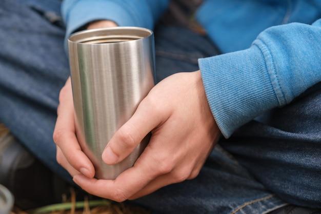 Tasse en acier inoxydable isolée dans les mains