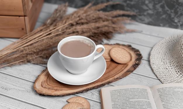 Une tasse d'américano ou d'espresso avec des biscuits, un livre et des roseaux. vue de dessus.
