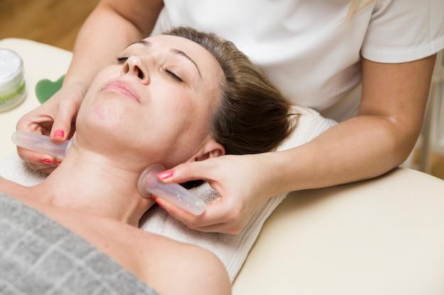 Tasse appliquée sur la peau du cou d'une patiente dans le cadre de la méthode traditionnelle de thérapie par ventouses