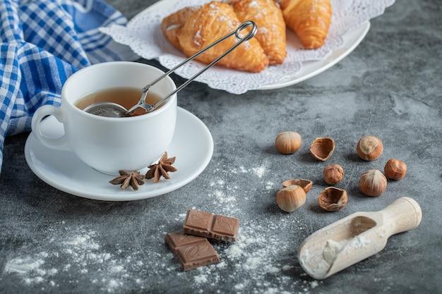 Tasse d'arôme de thé avec de délicieux croissants.