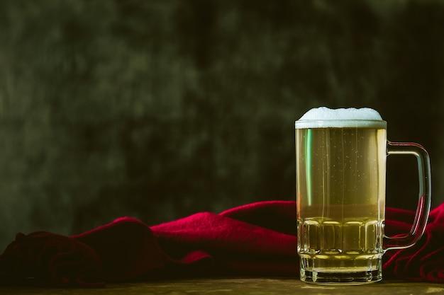 Tasse de bière avec une écharpe rouge sur la table en bois. espace libre pour le texte