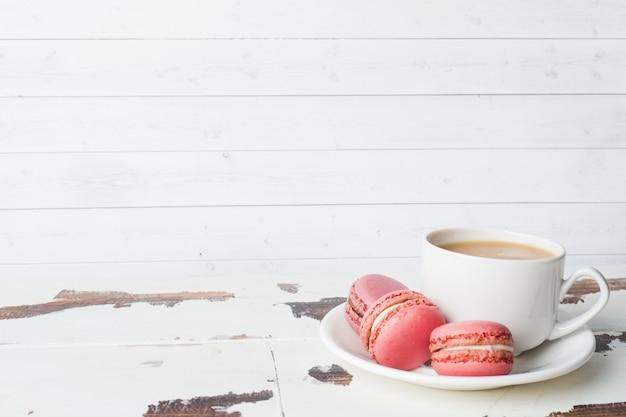 Tasse de biscuits au café et macaron sur une assiette sur un fond blanc. espace de copie