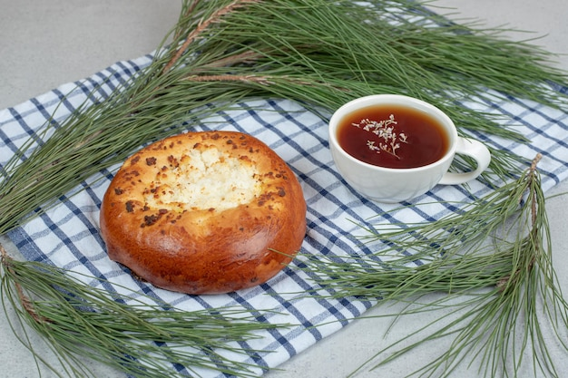 Tasse blanche d'arôme de tisane avec pâtisserie sur nappe.