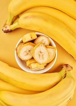 Tasse blanche avec des bananes tranchées sur fond jaune. fruits tropicaux, alimentation saine, vitamines