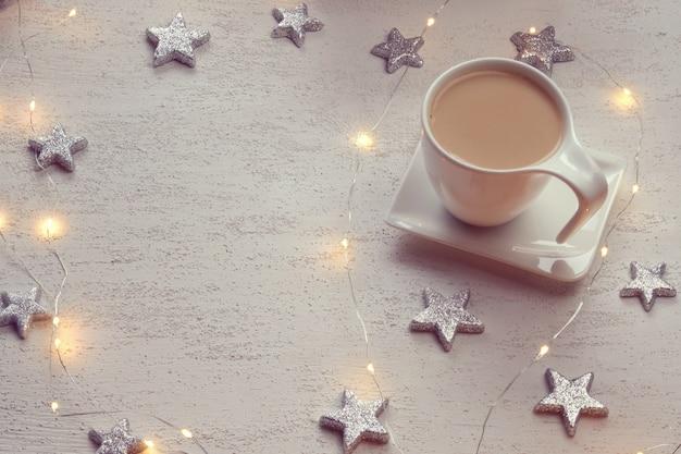 Tasse blanche avec cacao, étoiles décoratives argentées, guirlande brillante