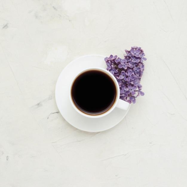 Tasse blanche avec un café et de belles fleurs lilas sur une surface blanche