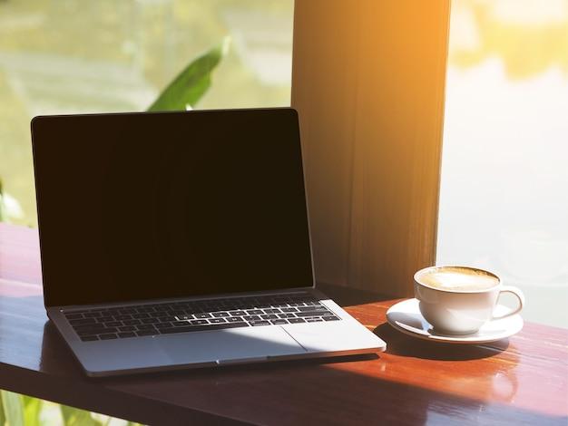 Tasse blanche, de, café cappuccino, et, ordinateur portable, sur, table, à côté de, fenêtre verre