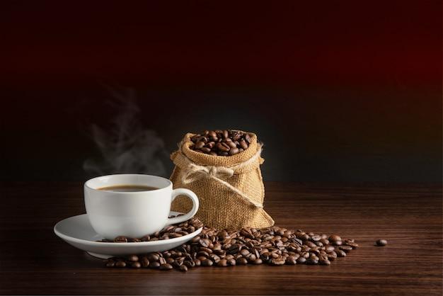 Tasse blanche de café chaud avec de la fumée avec des grains de café et un sac plein de grains de café avec une corde sur fond orange et noir