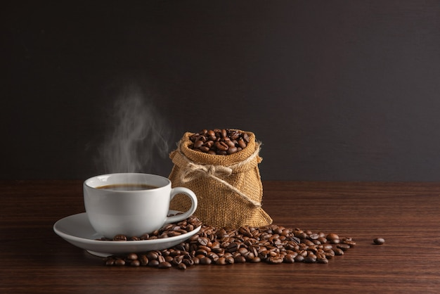 Tasse blanche de café chaud avec de la fumée avec des grains de café et un sac plein de grains de café avec une corde