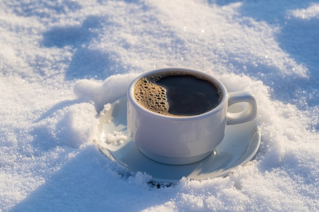 Tasse blanche de café chaud sur un lit de neige et fond blanc, gros plan. concept de matin d'hiver de noël