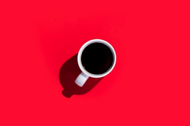 Tasse blanche avec un café sur un espace rouge isolé. vue de dessus, pose à plat