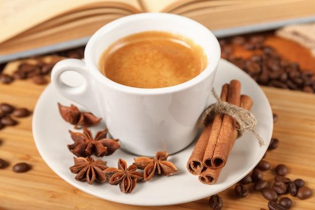 Tasse blanche de café expresso entourée de grains de café torréfiés