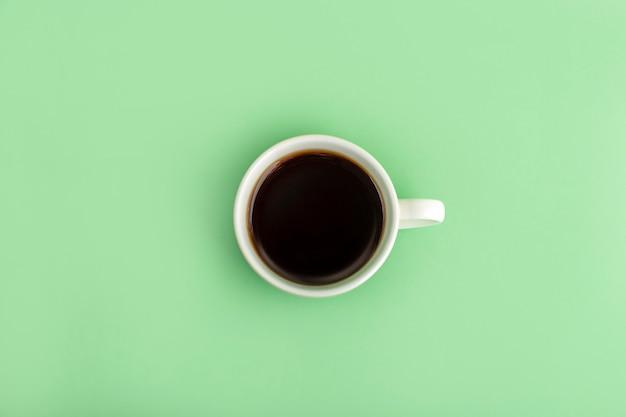 Tasse blanche avec café expresso noir sur vert