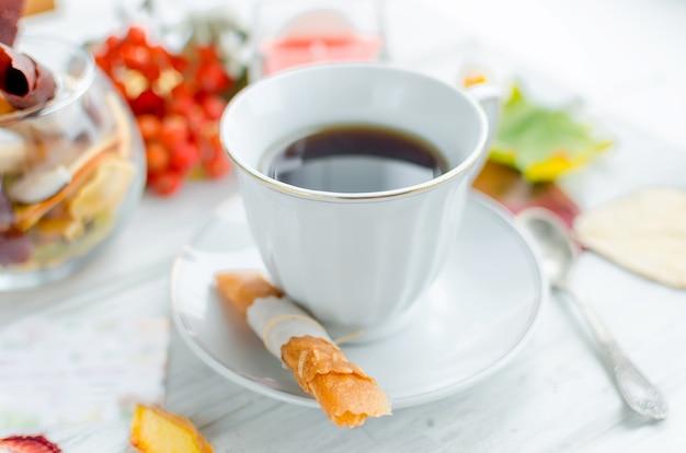 Tasse blanche de café et de fruits en cuir rouleaux et frites au petit déjeuner