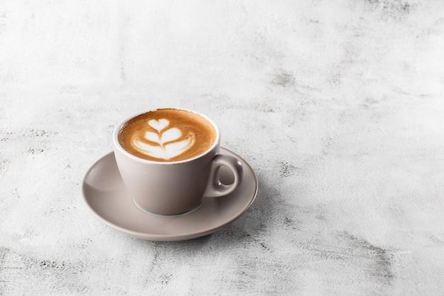 Tasse blanche de café latte chaud avec une belle texture d'art latte en mousse de lait isolée sur fond de marbre brillant. vue aérienne, espace copie. publicité pour le menu du café. menu du café. photo horizontale.